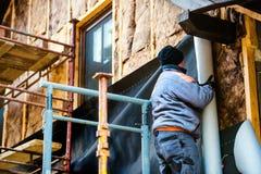 Trabajador de construcción que aísla termalmente la casa con las lanas de cristal Fotos de archivo