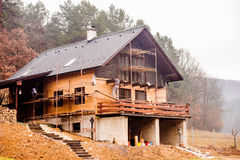 Trabajador de construcción que aísla termalmente la casa, haciendo el fac de madera Foto de archivo