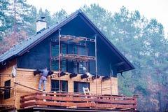 Trabajador de construcción que aísla termalmente la casa, haciendo el fac de madera Imagen de archivo