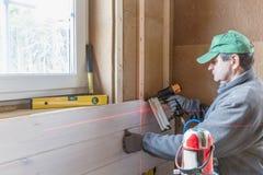 Trabajador de construcción que aísla termalmente la casa de marco de madera del eco Fotografía de archivo