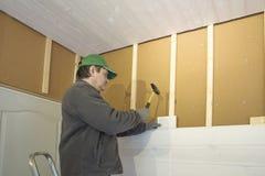Trabajador de construcción que aísla termalmente la casa de marco de madera del eco con las placas de madera de la fibra latvia Foto de archivo libre de regalías