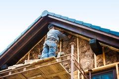 Trabajador de construcción que aísla termalmente la fachada de la casa con el vidrio Imágenes de archivo libres de regalías