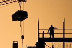 Trabajador de construcción que dirige la grúa con la carga Fotos de archivo libres de regalías