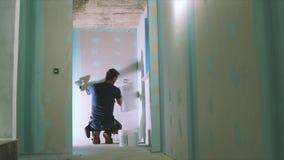 Trabajador de construcción que enyesa la pared del cartón yeso metrajes
