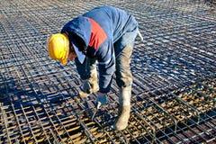 Trabajador de construcción que instala los alambres obligatorios Imágenes de archivo libres de regalías