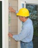 Trabajador de construcción que instala un marco de ventana Foto de archivo libre de regalías