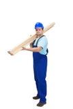 Trabajador de construcción que lleva plancks de madera Fotos de archivo