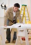 Trabajador de construcción que mira modelos Foto de archivo libre de regalías
