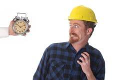 Trabajador de construcción que mira su reloj Foto de archivo libre de regalías