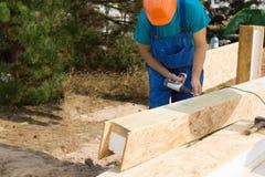 Trabajador de construcción que perfora un haz Imagen de archivo libre de regalías