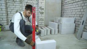 Trabajador de construcción que pone el bloque de cemento aireado según nivel de burbuja de aire almacen de video