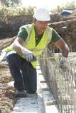 Trabajador de construcción que pone fundaciones imágenes de archivo libres de regalías