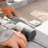 Trabajador de construcción que pone los adoquines de piedra en arena Imagen de archivo libre de regalías