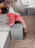 Trabajador de construcción que pone los adoquines de piedra en arena Imagen de archivo