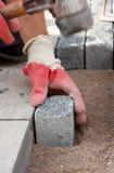 Trabajador de construcción que pone los adoquines de piedra en arena Foto de archivo libre de regalías