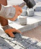Trabajador de construcción que pone los adoquines de piedra en arena Fotografía de archivo libre de regalías
