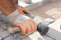 Trabajador de construcción que pone piedras clobble en arena Fotos de archivo