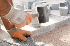 Trabajador de construcción que pone piedras clobble en arena Imagen de archivo libre de regalías