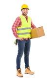 Trabajador de construcción que presenta con un paquete Imagenes de archivo