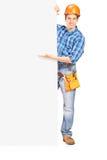 Trabajador de construcción que presenta detrás de un panel Imagen de archivo libre de regalías