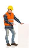 Trabajador de construcción que señala en el baner blanco. imágenes de archivo libres de regalías