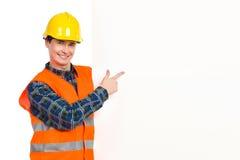 Trabajador de construcción que señala en la bandera. imagen de archivo