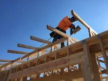 Trabajador de construcción que trabaja en el proceso que enmarca para un nuevo una casa Imagen de archivo
