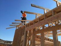 Trabajador de construcción que trabaja en el proceso que enmarca para un nuevo una casa Imagen de archivo libre de regalías
