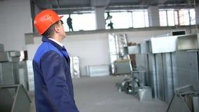 Trabajador de construcción que usa la tableta digital en sitio de trabajo Tubos de aire acanalados industriales metrajes