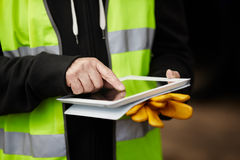 Trabajador de construcción que usa la tablilla digital Foto de archivo libre de regalías