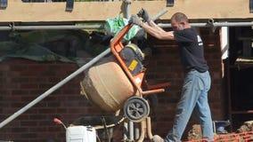 Trabajador de construcción que vacia el cemento del mezclador almacen de metraje de vídeo