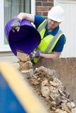 Trabajador de construcción que vacia la basura constructiva en salto fuera de la casa renovada foto de archivo