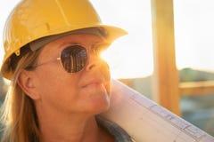 Trabajador de construcción de sexo femenino con planes de la casa en el emplazamiento de la obra fotos de archivo libres de regalías