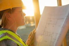Trabajador de construcción de sexo femenino con planes de la casa en el sitio de Construciton fotos de archivo
