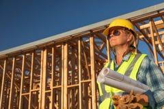 Trabajador de construcción de sexo femenino Holds Blueprints en el sitio de Construciton imagenes de archivo