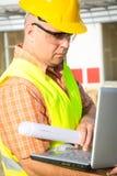 Trabajador de construcción Using Laptop Imagenes de archivo
