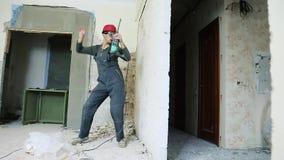 Trabajador de construcci?n con el perforador almacen de metraje de vídeo