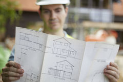 Trabajador de construcción On Building Site que mira planes de la casa Fotos de archivo