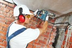 Trabajador de construcción con el perforador del taladro Foto de archivo libre de regalías