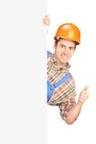 Trabajador de construcción joven con el casco que presenta detrás de un panel y Imágenes de archivo libres de regalías