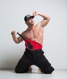 Trabajador de construcción muscular en guardapolvos Arrodillamiento Fotografía de archivo