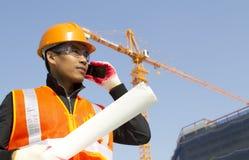 Trabajador de construcción con la grúa en fondo Imágenes de archivo libres de regalías