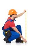 Trabajador de construcción que mide la pared Fotos de archivo libres de regalías
