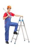 Trabajador de construcción que presenta en una escalera Imágenes de archivo libres de regalías