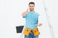 Trabajador de Construciton con el ordenador portátil que gesticula los pulgares para arriba Imágenes de archivo libres de regalías