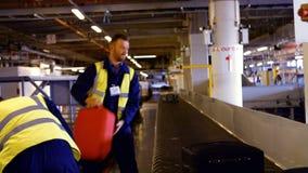 Trabajador de dos aeropuertos que pone equipaje en el carrusel del equipaje almacen de video