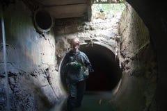 Trabajador de la alcantarilla en colector subterráneo inundado de las aguas residuales imagen de archivo