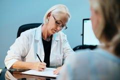 Trabajador de la atención sanitaria que habla con el paciente mayor enfermo en hospital imagenes de archivo