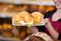 Trabajador de la cafetería que detiene a Tray Full Of Burgers Foto de archivo