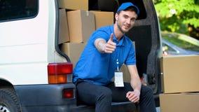 Trabajador de la compañía móvil que muestra los pulgares para arriba, sentándose en furgoneta por completo de las cajas de cartón fotos de archivo libres de regalías